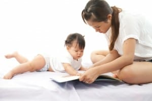 Mother Is Reading A Book For Her Baby Stock Photo